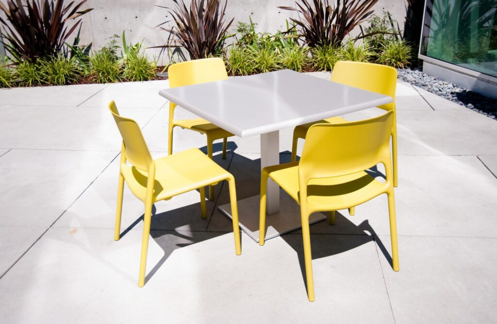 a stainless steel table and yellow chairs